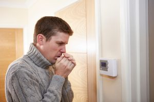 man looking cold, standing in front of a thermostat