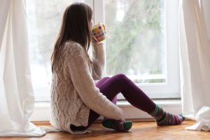 young woman dressed for cold weather sitting by the window having hot drink