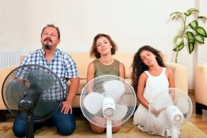 family sitting in front of fans cooling off