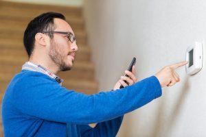 man-adjusting-programmable-thermostat