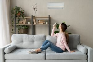 woman-sitting-on-couch-turning-on-ductless-air-handler-with-remote